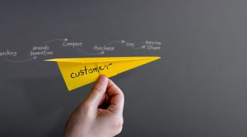 customer-journey-experience-concept-hand-raise-up-paper-plane-against-wall